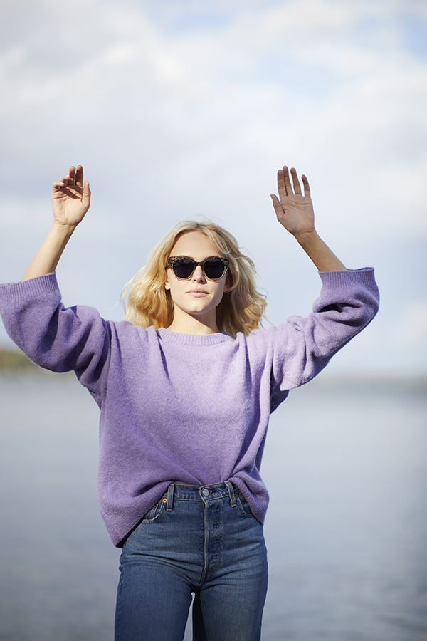 Woman in lavendel top, jeans and sunglasses