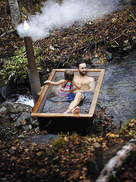 Man and child in outdoor bathtub