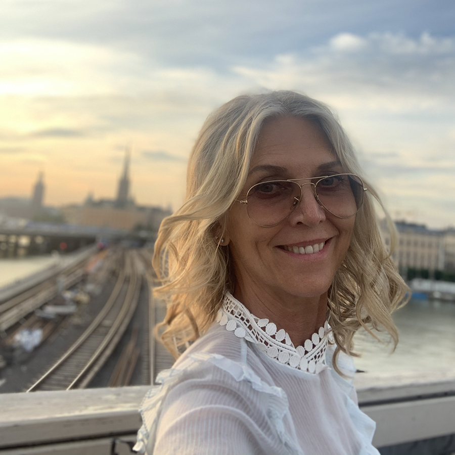 Lotta Ahlvar wearing a white blouse and eyewear in Stockholm